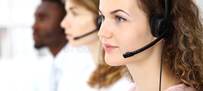 Center operatör för ett felanmälan Ung härlig brunettkvinna i hörlurar med mikrofon äganderätt för home tangent för affärsidé som fotografering för bildbyråer
