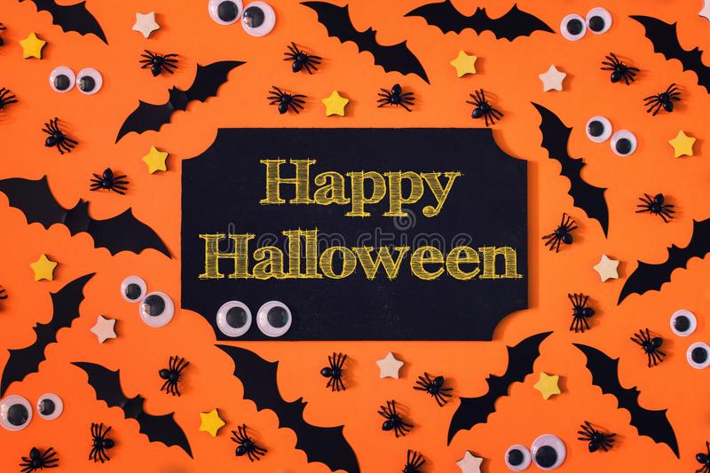 In the center of the orange background a sign with the inscription of the Happy Halloween. Around it are small. Decorative bats, spiders and puppet eyes. A stock image