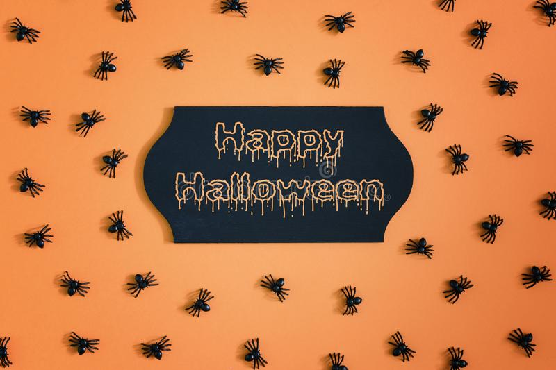 In the center of the orange background a signboard with the inscription Happy Halloween. Around are scattered small. Decorative spiders. An unusual photo from royalty free stock photography