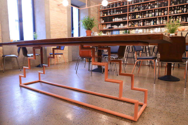In center of photo unusual table in middle of modern restaurant. In middle of establishment, cafe or restaurant table with wooden lacquered top on unusual metal stock image