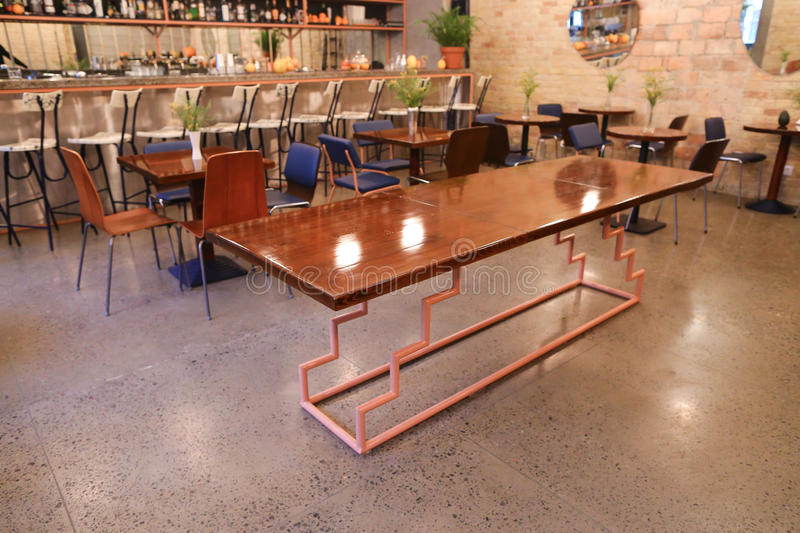 In center of photo unusual table in middle of modern restaurant. In middle of establishment, cafe or restaurant table with wooden lacquered top on unusual metal stock photos