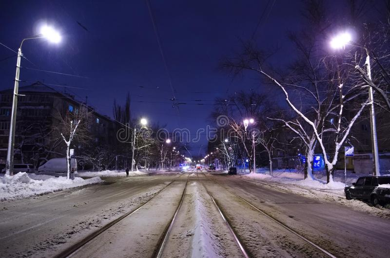 Center of the snowy road with rails. The night city with night traffic. stock images