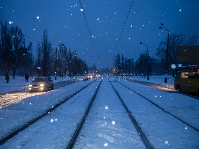 Center of the snowy road with rails. The night city with snowfall. stock images
