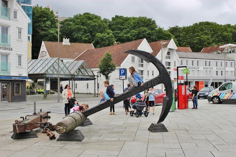 In the center of Stavanger, Norway, Europe. STAVANGER, NORWAY - AUGUST 5, 2015: Children are using a large anchor in the Vagen marina of Stavanger as a slide royalty free stock image