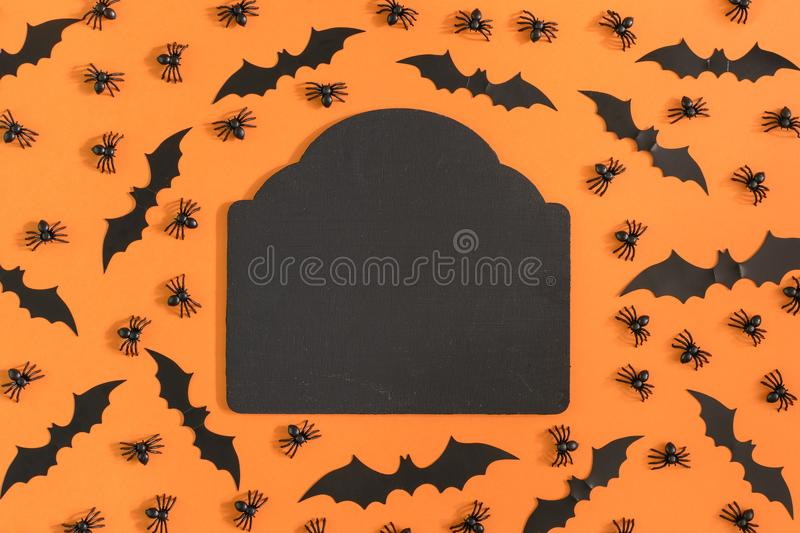 In the center there is a figured black tablet. Around are decorated with decorative spiders and halloween bats. Photo royalty free stock photo