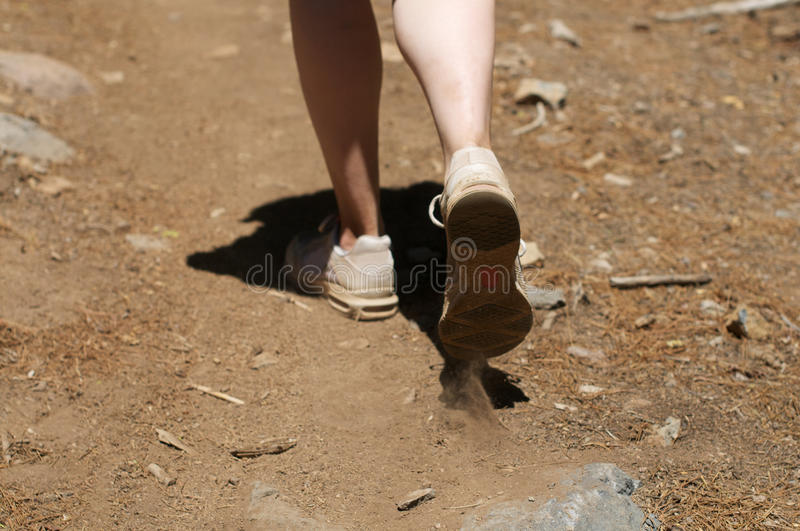 Centered close up of woman's feet hiking in dirt royalty free stock photos