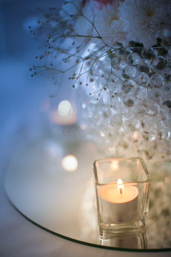 Centerpiece kwiaty w wazie na błękitnym wieczór i świeczka zaświecamy zdjęcie royalty free