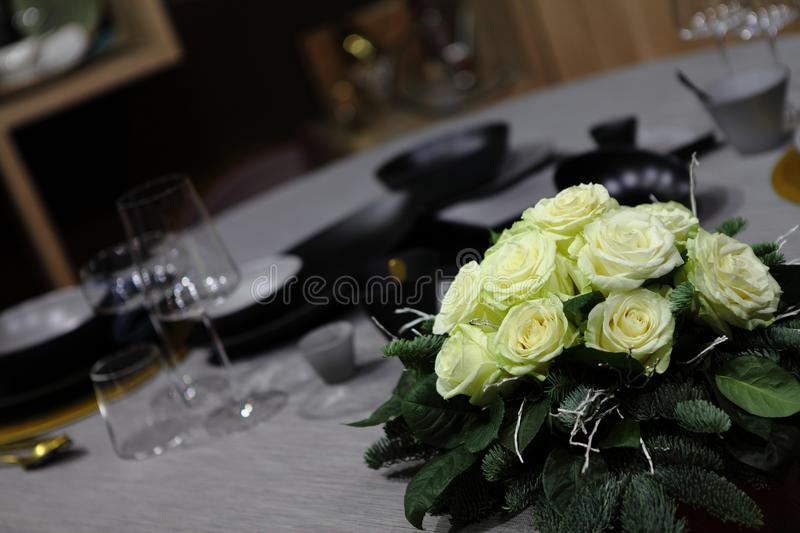 Centerpiece of roses on the table. In the foreground the center table of white roses and in the background the set table royalty free stock image