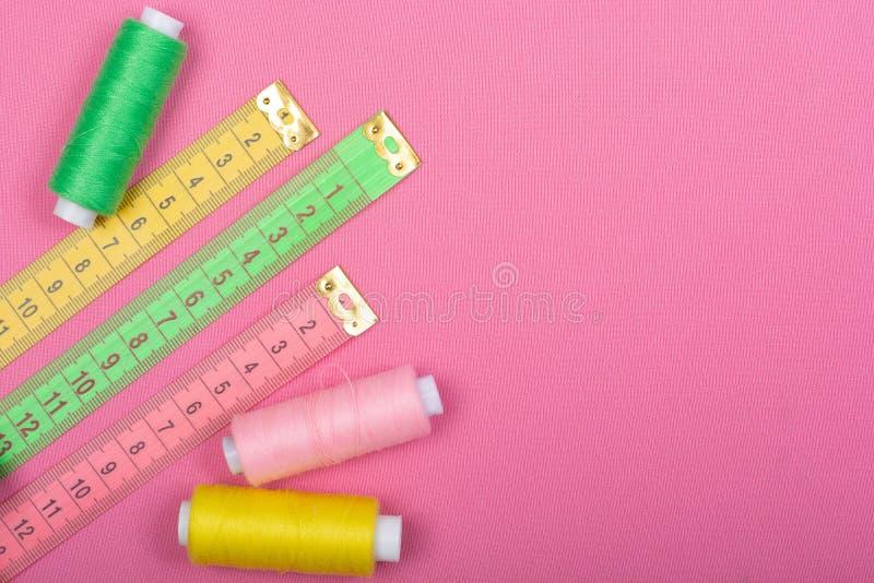 Centimeter en rollen met draden van groen, roze en geel op een roze achtergrond royalty-vrije stock fotografie