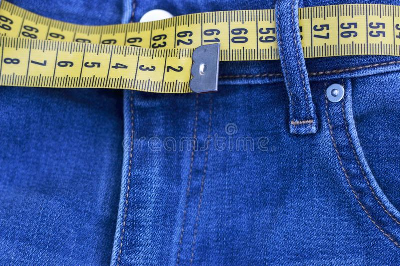 Centimeter tape, measuring as belt in jeans close-up, concept of losing weight. Healthy lifestyle. Centimeter tape, measuring as belt in jeans close-up, concept royalty free stock photo