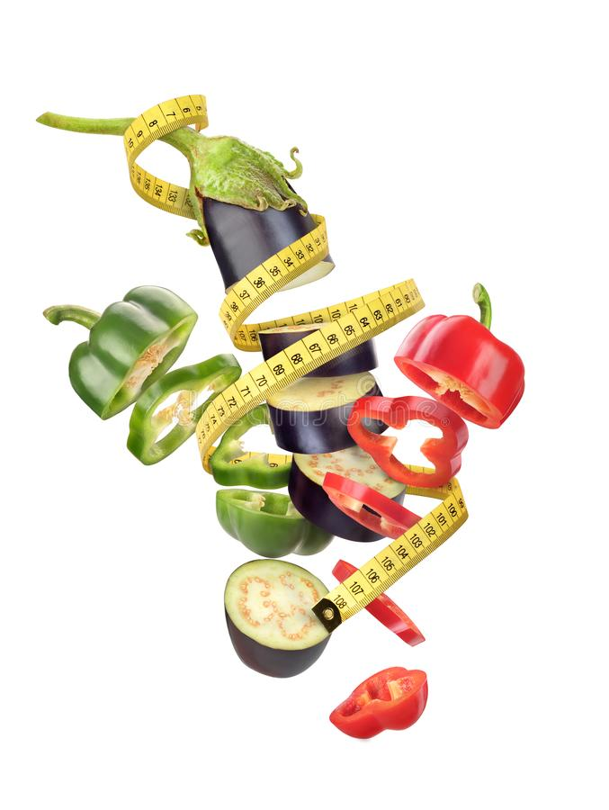 Centimeter tape with vegetables. Pepper. Eggplant. Isolated on White Background royalty free stock photography