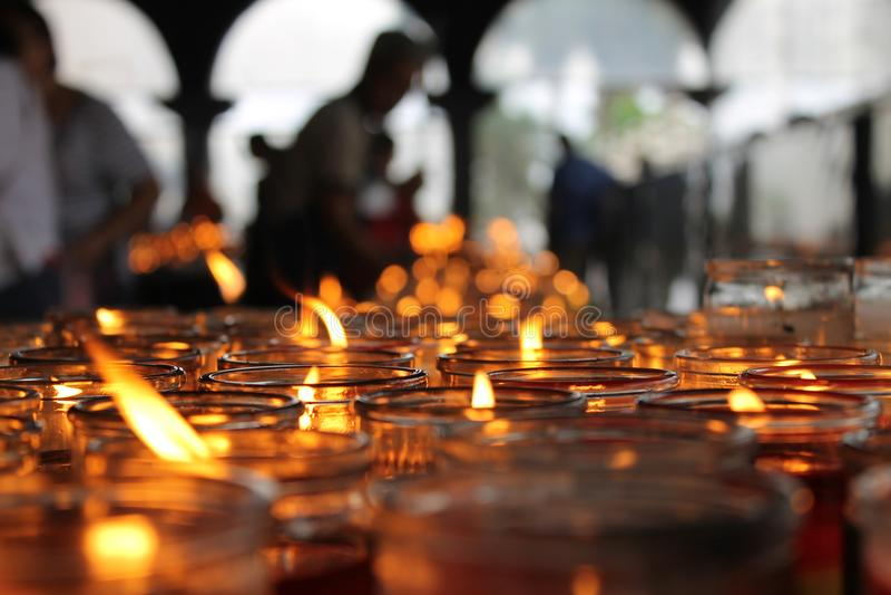 Centinaia di candele religiose con fondo unfocoused immagini stock