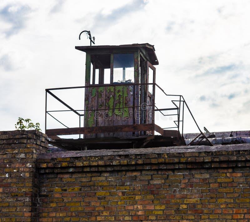 Centinela-caja vieja en la pared de ladrillo de la planta industrial imagen de archivo