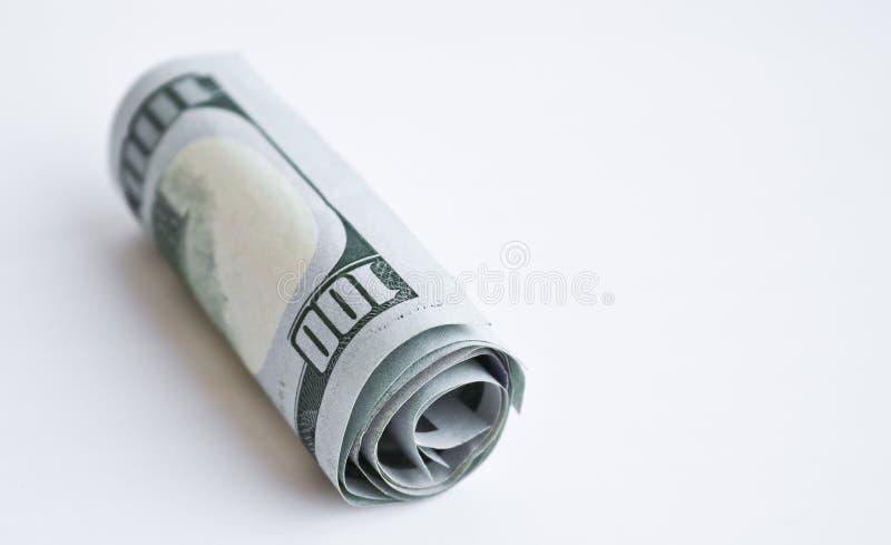 Cento banconote in dollari hanno rotolato in un tubo fotografia stock