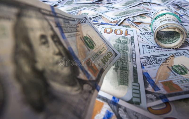 Cento banconote in dollari sui precedenti del mucchio del dollaro fotografia stock