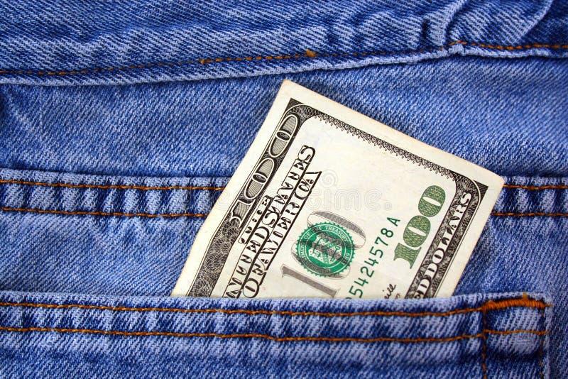 Cento fatture del dollaro in casella dei jeans fotografia stock