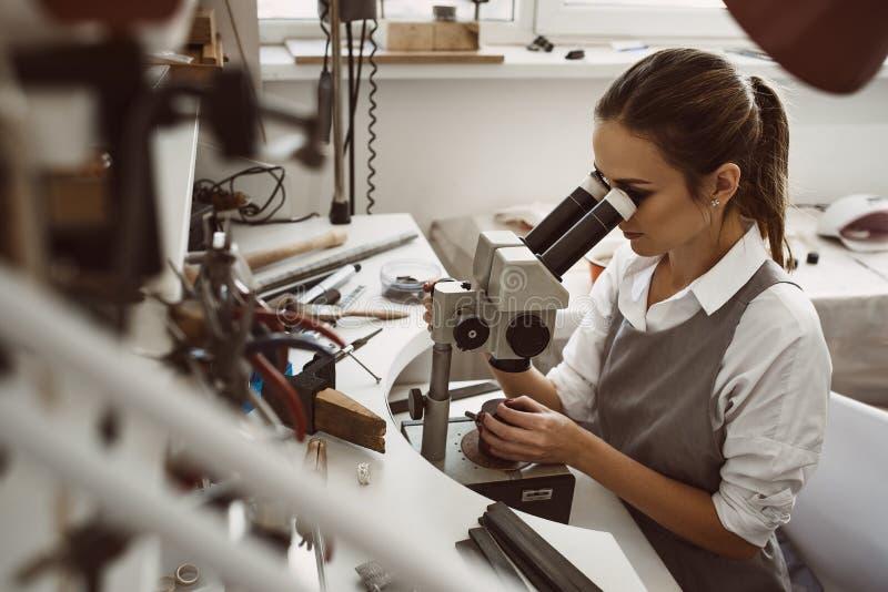 Centrado sobre o trabalho Retrato do joalheiro fêmea novo que olha o produto novo da joia através do microscópio em uma oficina imagem de stock royalty free