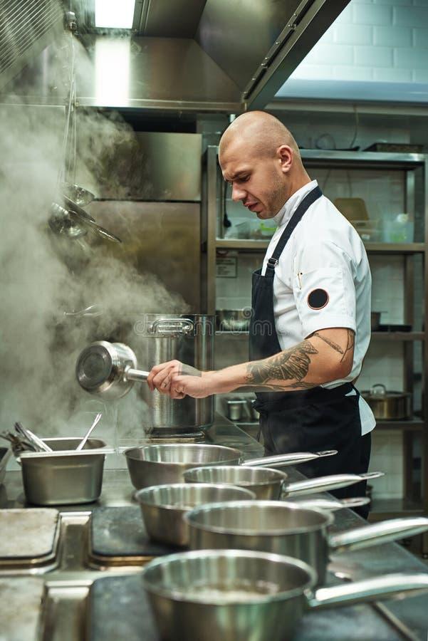 Centrado sobre um processo Opinião lateral o cozinheiro chefe considerável e novo que cozinha a massa italiana caseiro em uma coz foto de stock