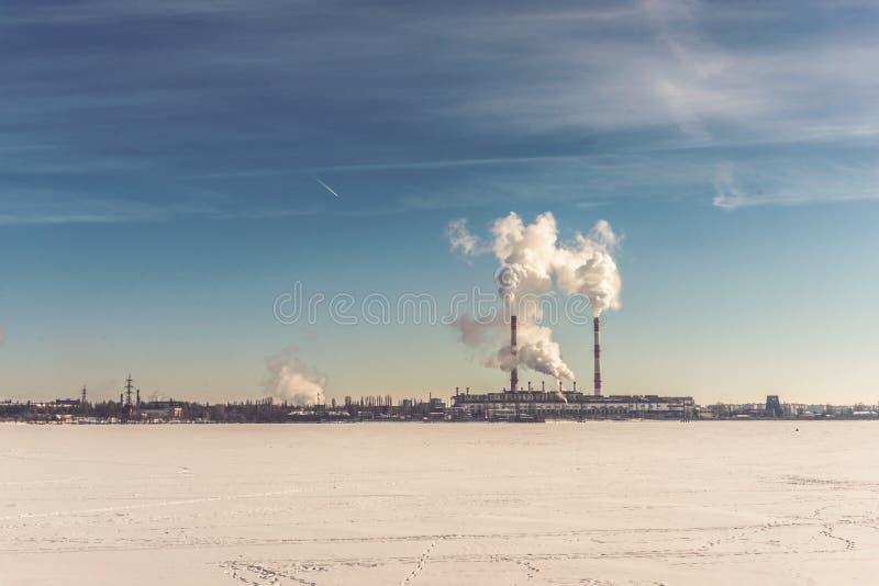 Central eléctrica, área de la central eléctrica de la energía en el río congelado o lago en el cielo azul imágenes de archivo libres de regalías