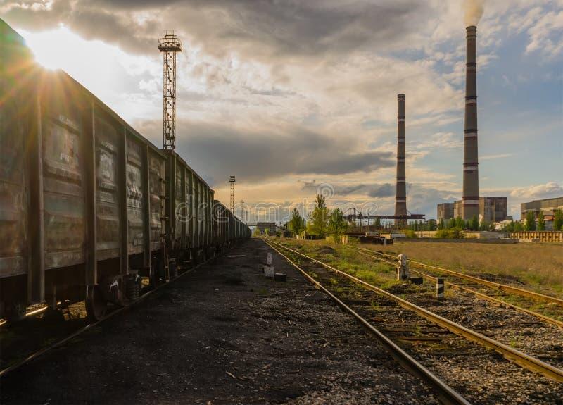 Central eléctrica de energía del carbón con el tren de cielo nublado de la puesta del sol fotos de archivo libres de regalías