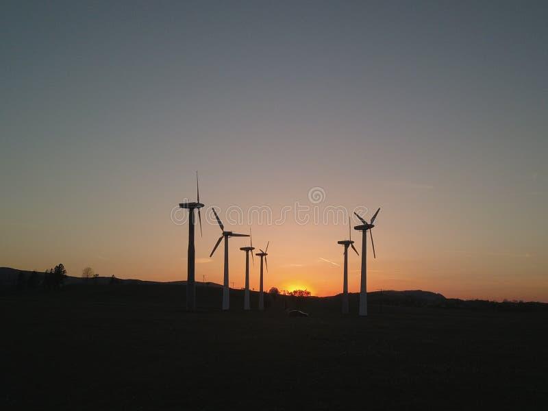 Central eléctrica de energía eólica en la puesta del sol Cuchillas giratorias de los generadores de la energía Limpie ecológicame imagenes de archivo