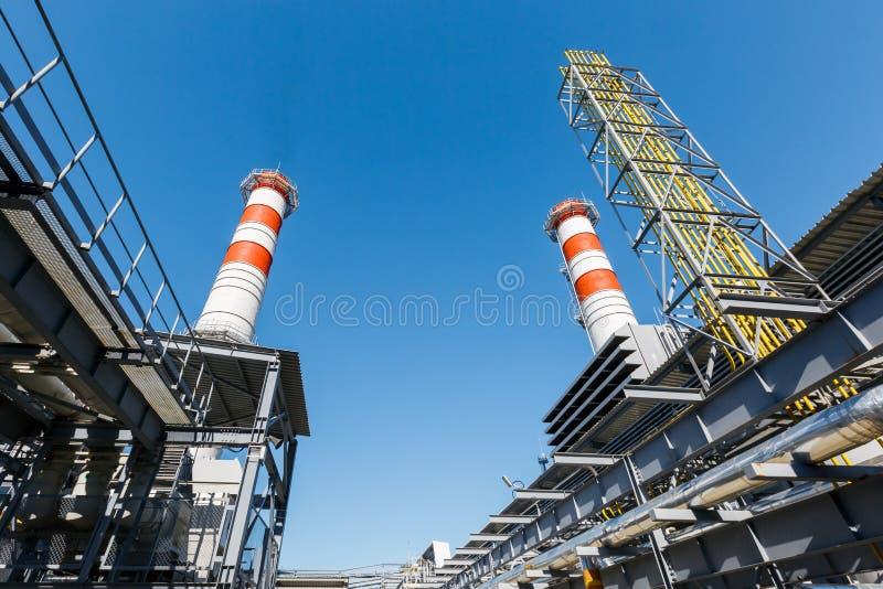 Central el?ctrica de la turbina de gas en el gas natural con las chimeneas del color rojo-blanco contra un cielo azul en un d?a s foto de archivo