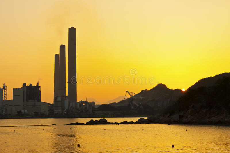 Central eléctrica a lo largo de la costa en la puesta del sol en Hong-Kong imágenes de archivo libres de regalías