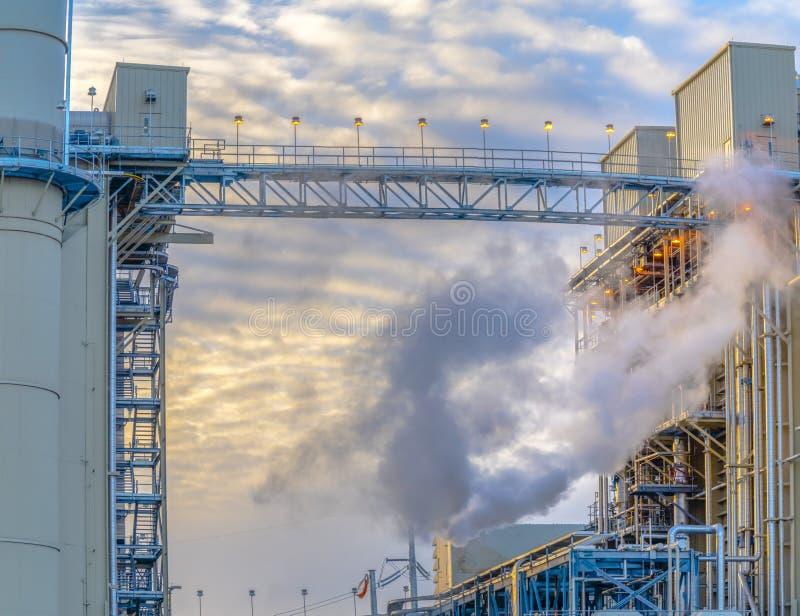 Central eléctrica que emite humo con el fondo nublado del cielo azul en un día soleado imagen de archivo libre de regalías