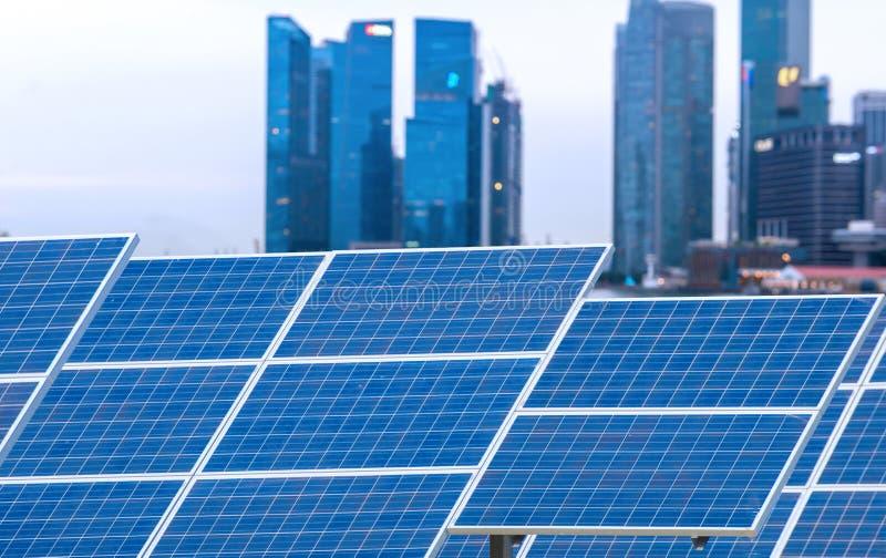 Central eléctrica usando energía solar renovable con la ciudad que construye detrás imágenes de archivo libres de regalías