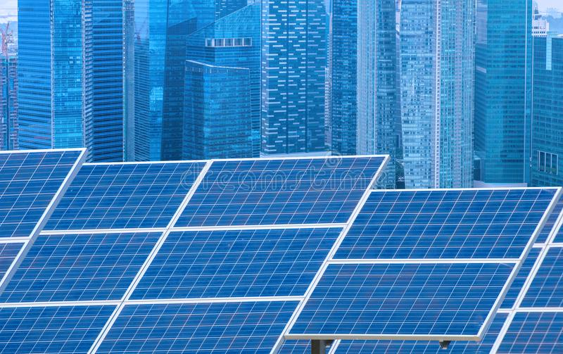 Central eléctrica usando energía solar renovable con la ciudad que construye detrás fotografía de archivo libre de regalías