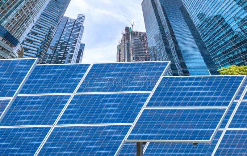 Central eléctrica usando energía solar renovable con la ciudad que construye detrás foto de archivo