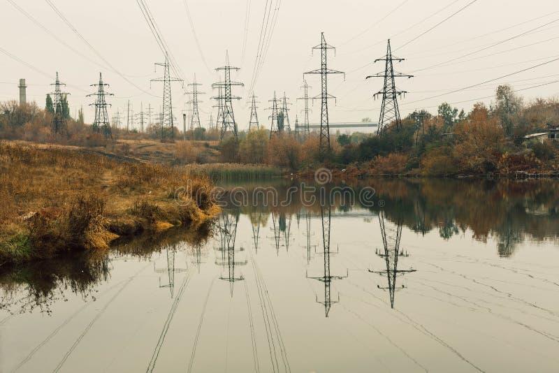 Central elétrica de carvão na área bonita completa das árvores e do lago, reflexão de espelho do polo energético e central elétri imagens de stock