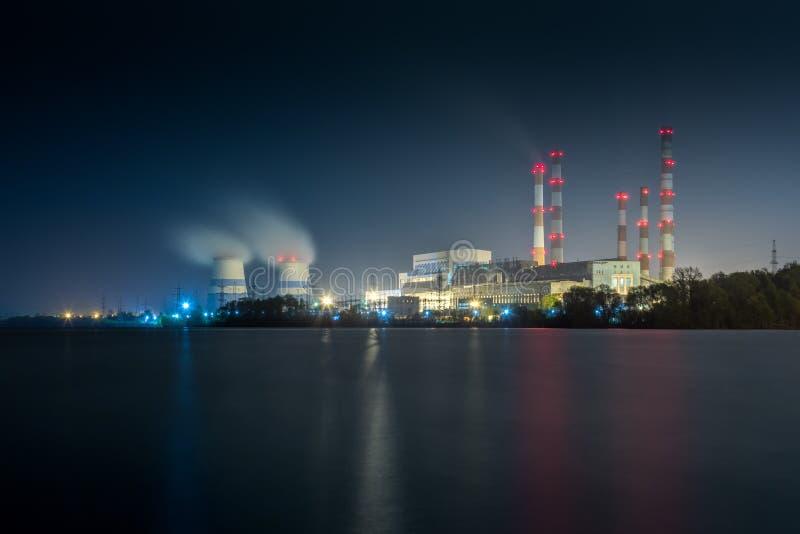 Central elétrica térmico velho de 450 megawatt na noite com o lago artificial no primeiro plano imagem de stock