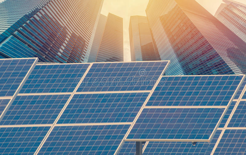 Central elétrica usando a energia solar renovável com a cidade que constrói para trás fotografia de stock royalty free