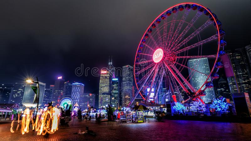 People ride ferris wheel in front of Hong Kong Business District at Night royalty free stock photography