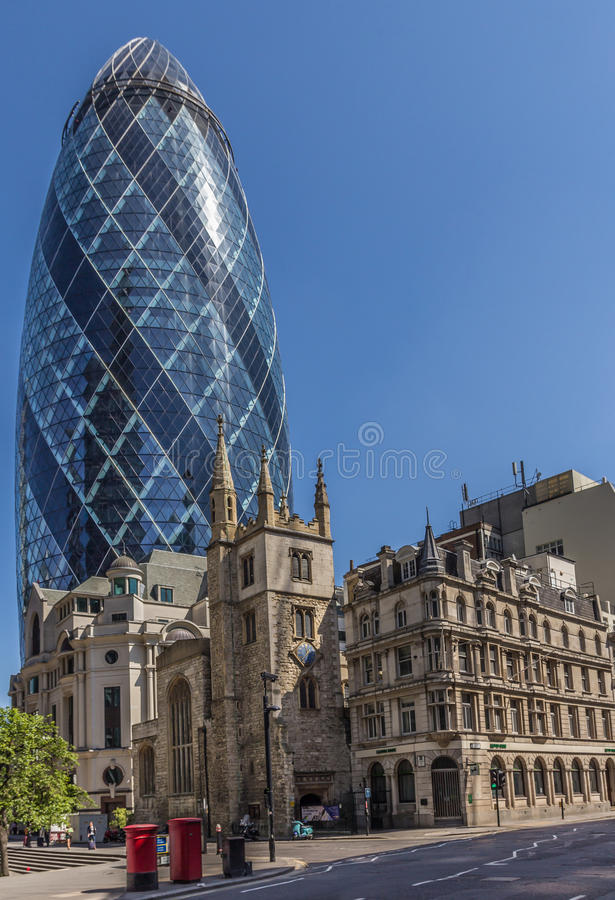 CENTRAL LONDON / ENGLAND - 18.05.2014 - The Gherkin sky-scraper is seen behind the St. Andrew Undercroft medieval church in London. The Gherkin sky-scraper is stock photos