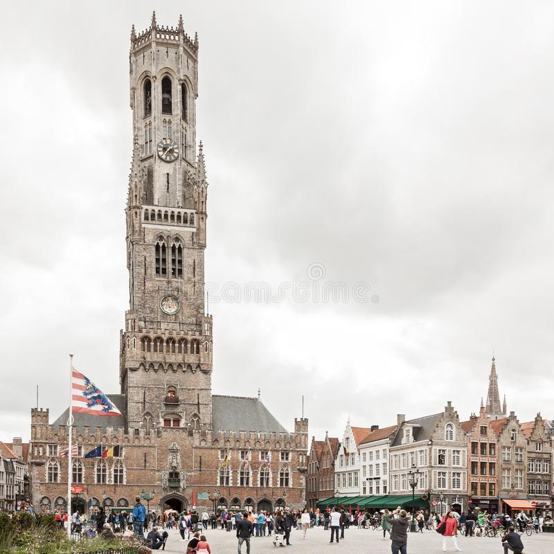 Central market square and Belfort tower in Bruges Belgium. Bruges, Belgium - 27 August, 2018: Central market square Grote markt and Belfort tower with tourists stock image