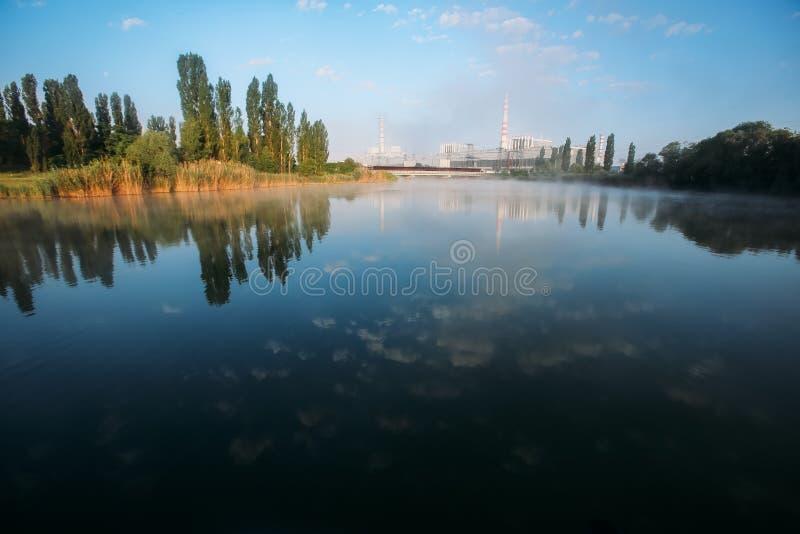 Central nuclear en la mañana Paisaje industrial con el lago y los árboles fotos de archivo libres de regalías