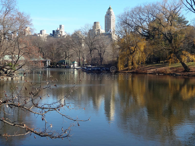Central Park Lake in Winter. With the Loeb Boathouse and New York City skyline in the distance stock photo