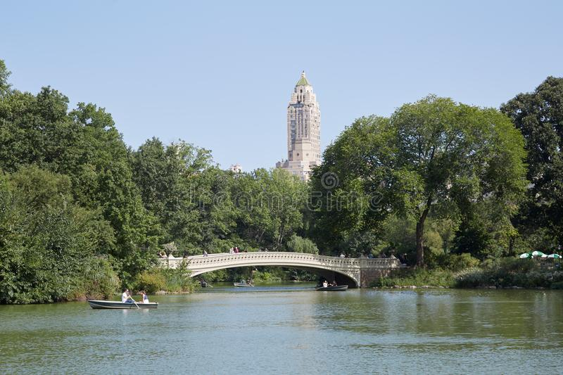 Central Park white Bow bridge with people and pond in New York stock photography