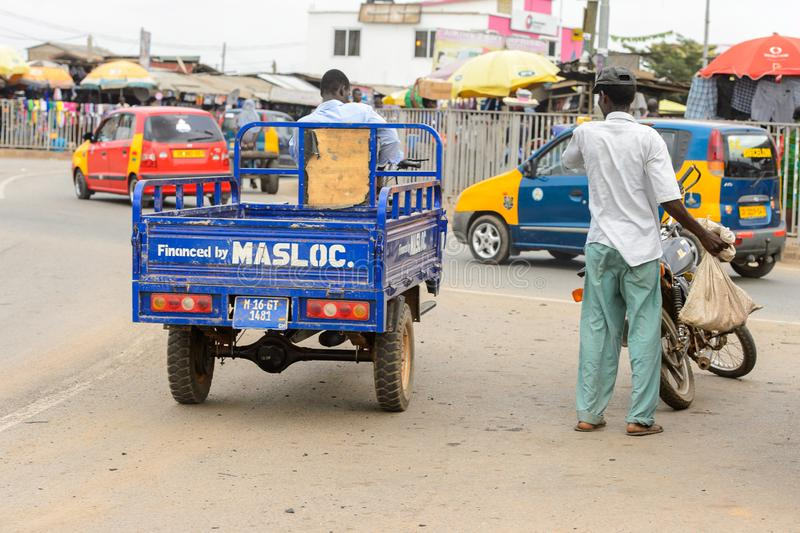 Unidentified Ghanaian man drives a tricycle in local village. P. CENTRAL REGION, GHANA - Jan 17, 2017: Unidentified Ghanaian man drives a tricycle in local royalty free stock photography