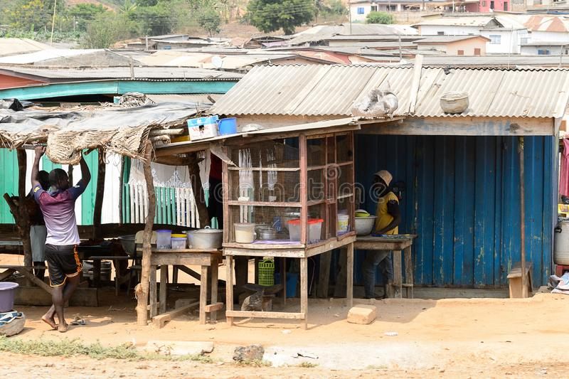 Unidentified Ghanaian man holds on the roof of outbuilding in l. CENTRAL REGION, GHANA - Jan 17, 2017: Unidentified Ghanaian man holds on the roof of outbuilding stock photography