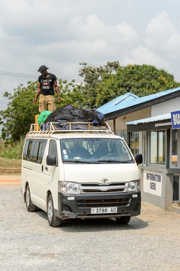 Unidentified Ghanaian man stands on the roof of the car in loca. CENTRAL REGION, GHANA - Jan 17, 2017: Unidentified Ghanaian man stands on the roof of the car in royalty free stock image