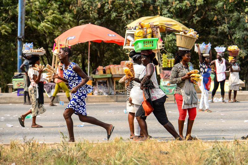 Unidentified Ghanaian people walk along the market in local vil. CENTRAL REGION, GHANA - Jan 17, 2017: Unidentified Ghanaian people walk along the market in royalty free stock images