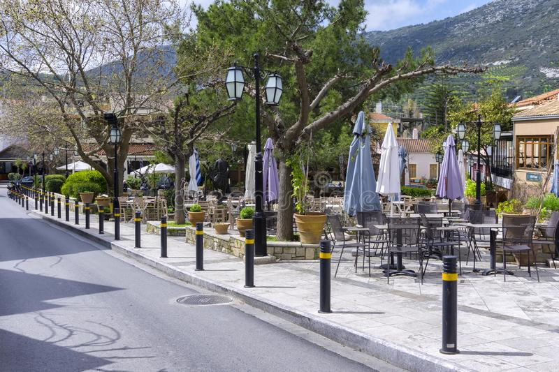 Central Square of Archanes village with the old traditional coffee shops and restaurants. Archanes, Crete island / Greece - March 20, 2019: Central Square of stock photography
