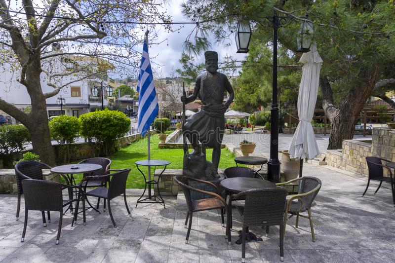 Central Square of Archanes village with the traditional coffee shops. Bronze statue of a cretan hero. Archanes, Crete Island / Greece - March 20, 2019: Central stock photos