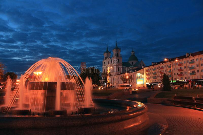 Central square in Grodno. The central square in Grodno with a fountain in the evening royalty free stock photo