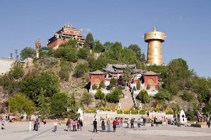 Central Square in Shangri-La. The bustling central square in the old town of Shangri-La with a giant Buddhist prayer wheel and Buddhist temple on the small hill royalty free stock images