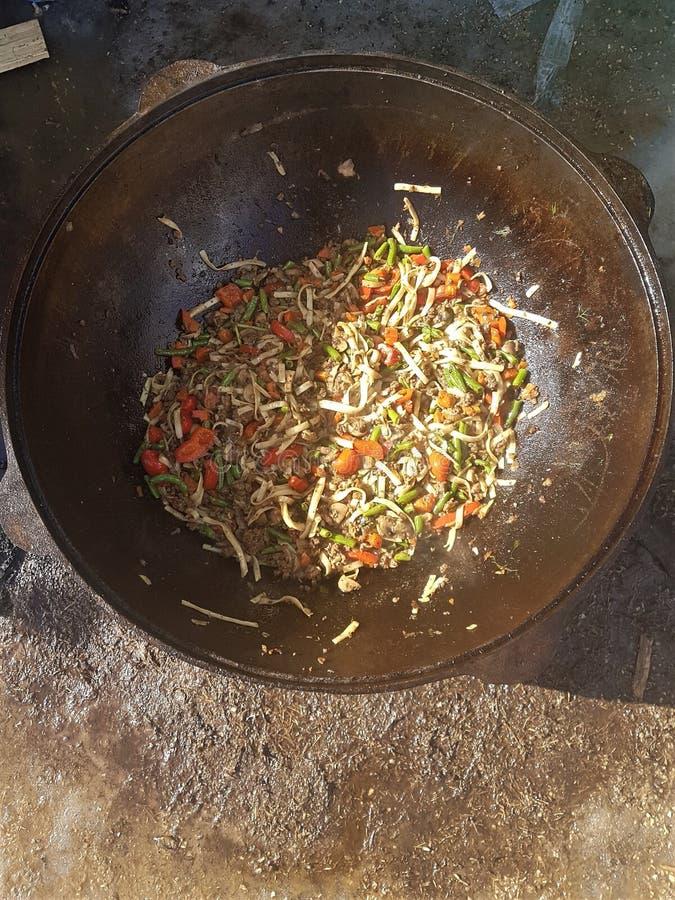 Centrale Aziatische keuken - hoogste mening van hete gekookte pottage van lam en groenten in gietijzerketel stock fotografie
