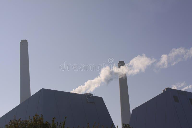 Centrale elettrica moderna con il camino e la colonna di fumo retroilluminati contro un cielo blu con lo spazio della copia fotografia stock libera da diritti
